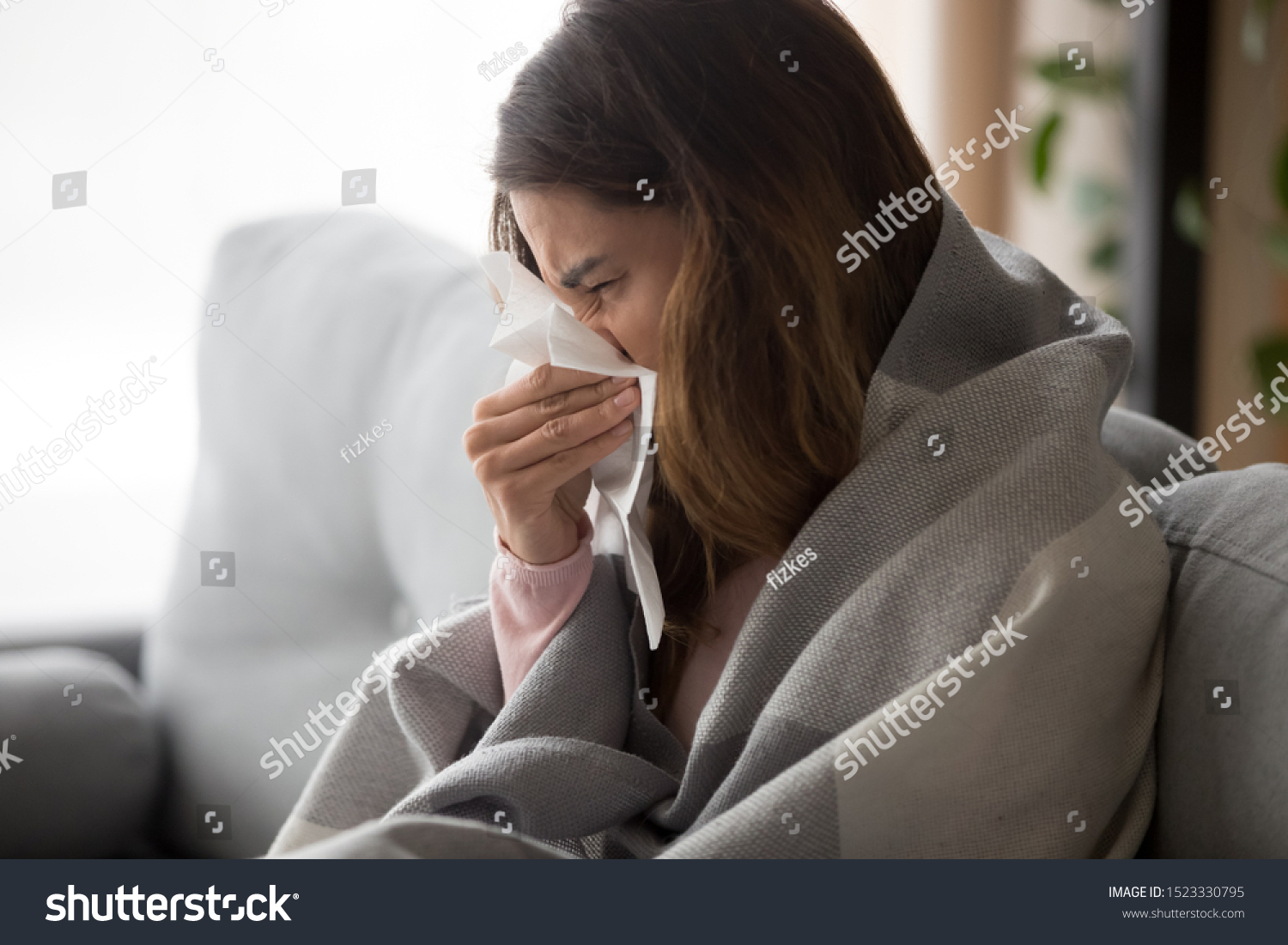 Ill upset young woman sitting on sofa covered with blanket freezing blowing running nose got fever caught cold sneezing in tissue, sick girl having influenza symptoms coughing at home, flu concept #1523330795