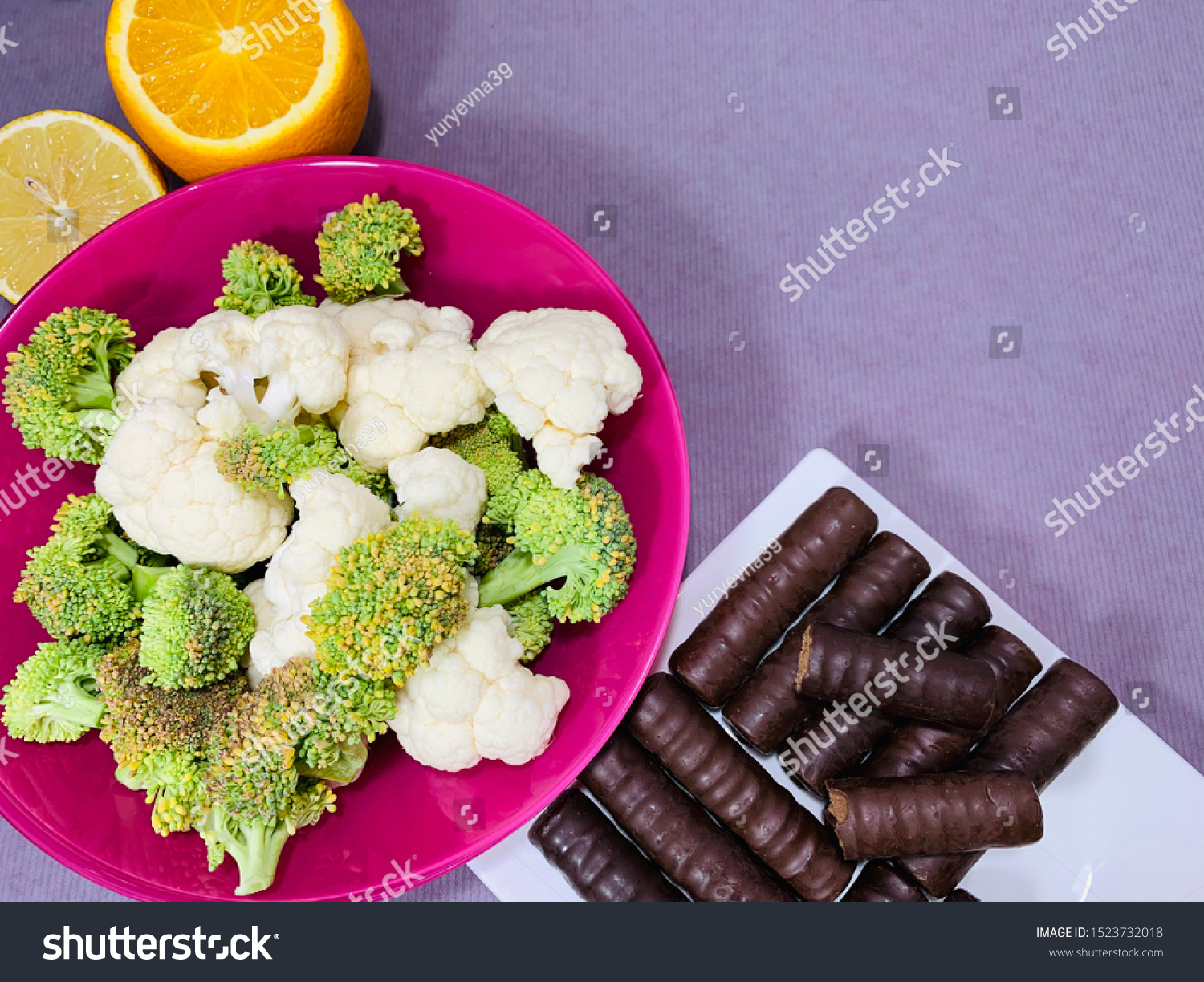Choice of food, broccoli and chocolate. Plate with vegetables, fruits. Chocolate is a junk food. Choosing a healthy diet. On a diet. #1523732018