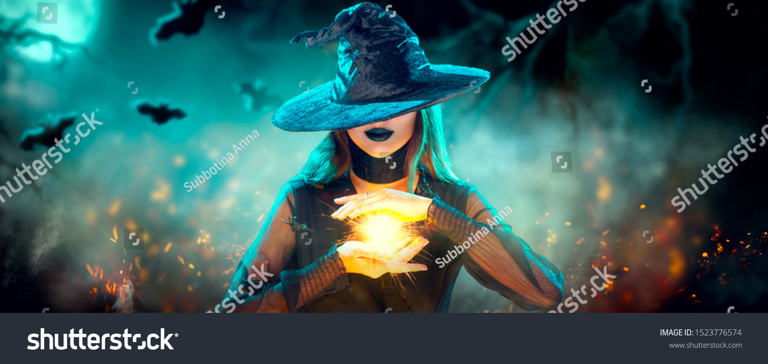 Halloween Witch girl with making witchcraft, magic in her hands, spells. Beautiful young woman in witches hat conjuring. Spooky dark magic forest background. Magician. Wide Halloween party art design #1523776574