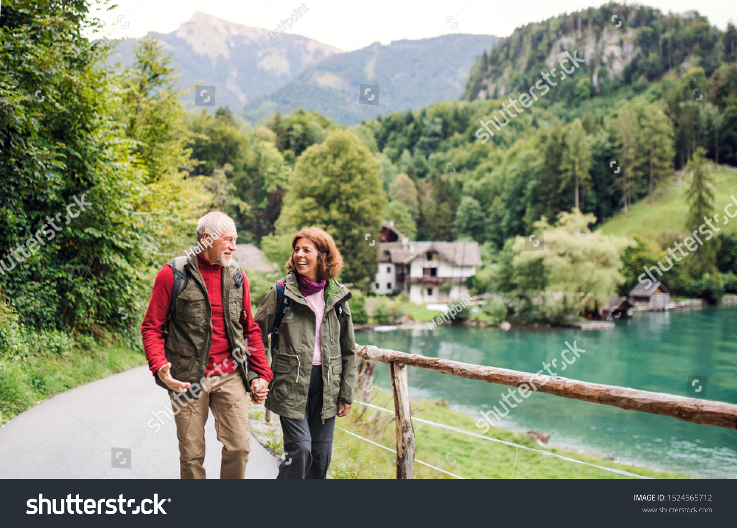 A senior pensioner couple hiking in nature, holding hands. #1524565712