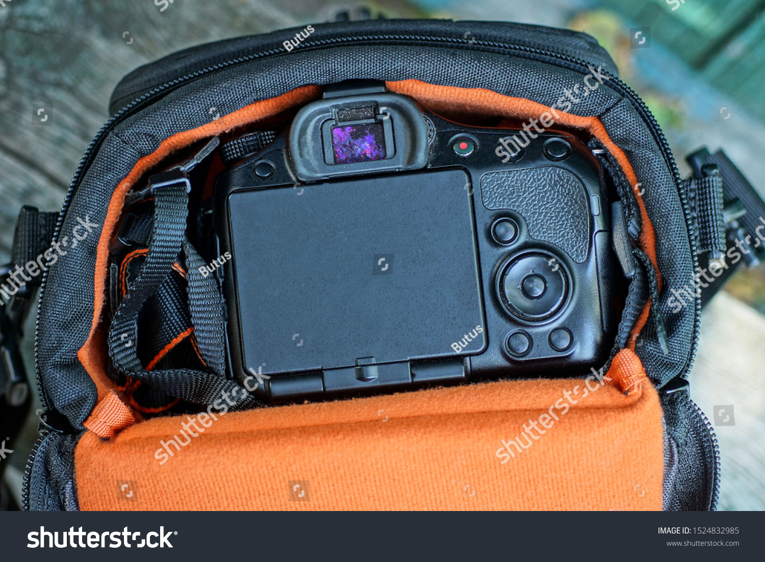 one orange bag with a black camera on a gray table #1524832985