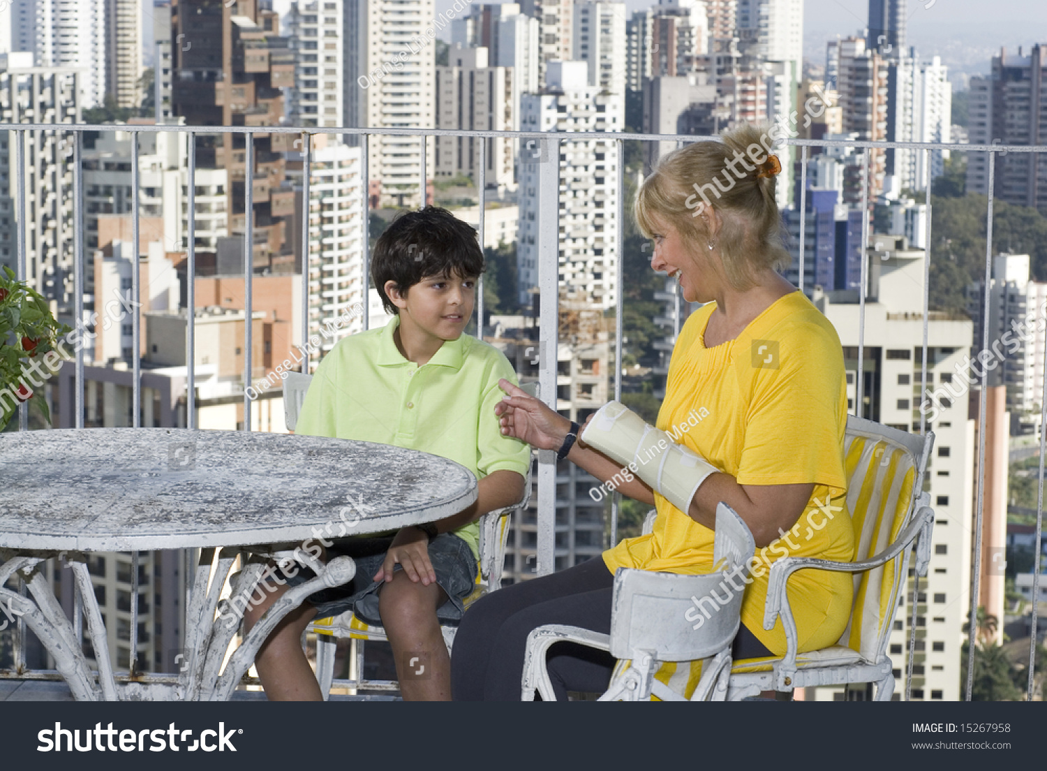 Woman sitting next to boy on balcony overlooking city for Balcony overlooking city