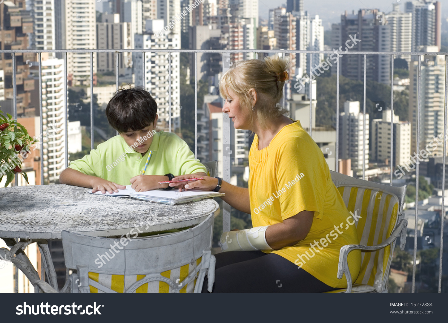 Woman watching or helping boy write woman and boy sitting for Balcony overlooking city