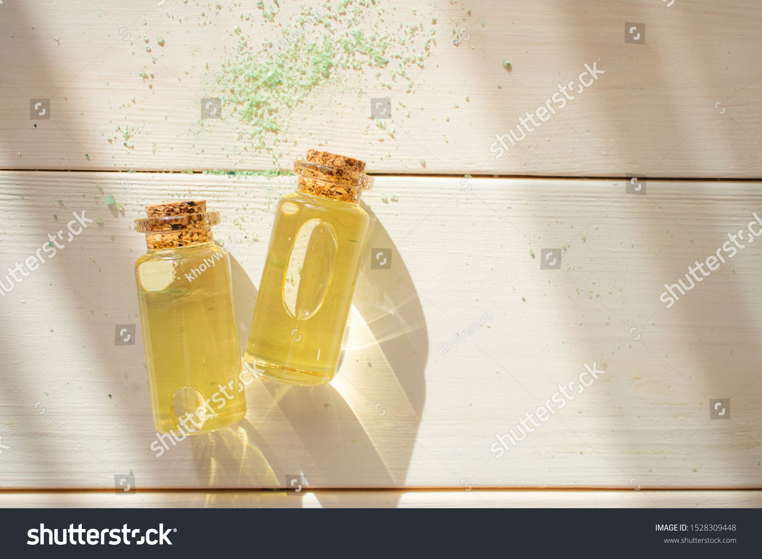 The concept of aromatherapy, relaxation, organics. Transparent bottles with essential oil on a light wooden background. Organic apothecary. Place for text. Minimalism, bright sunlight. #1528309448