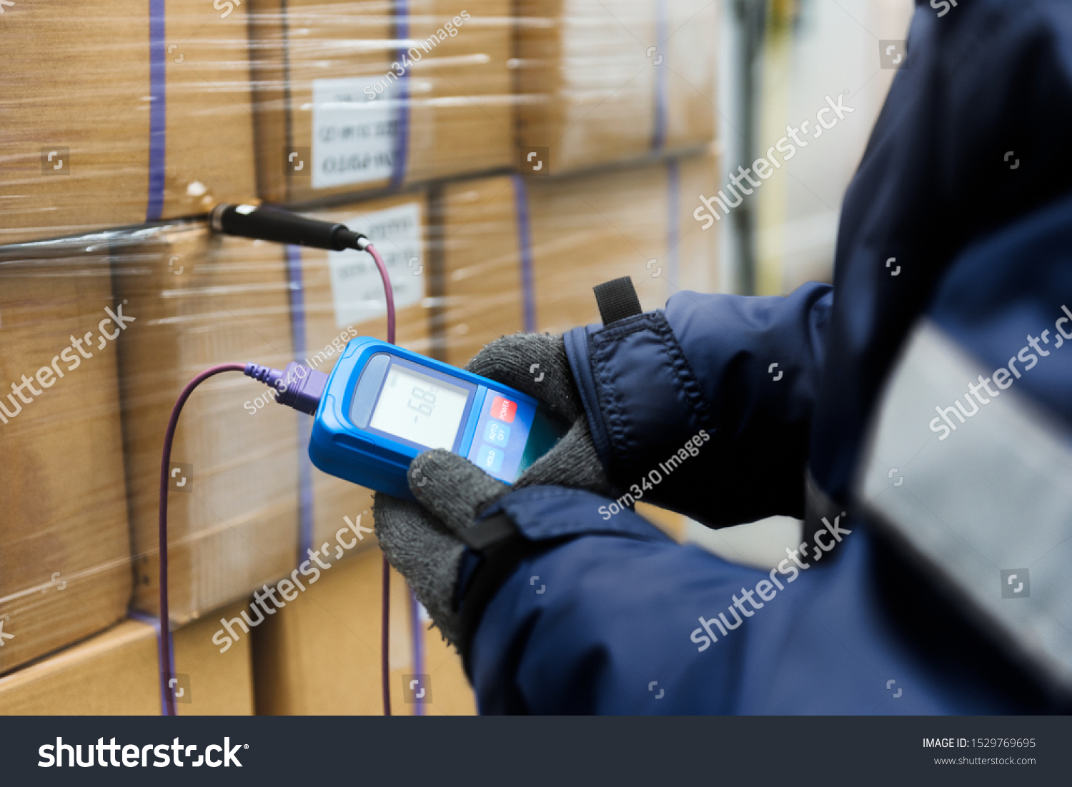 Hand of worker using thermometer to temperature measurement in the goods boxes with ready meals after import in the cold room or warehouse for keep temperature room #1529769695