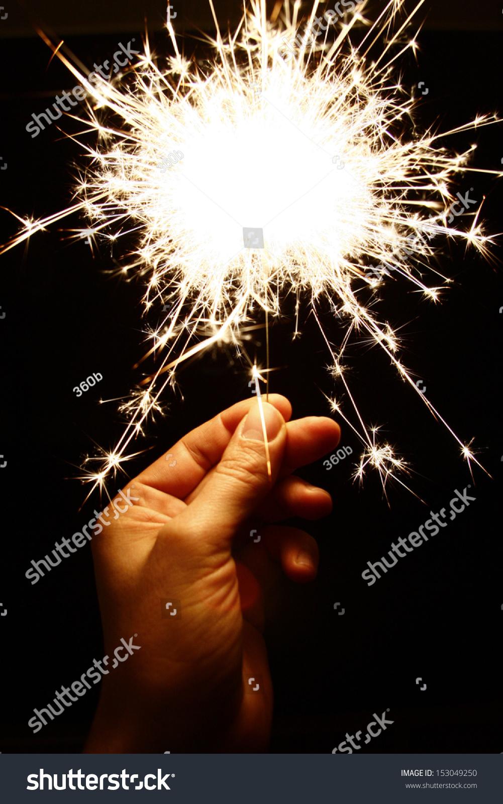 hand holding a sparkler symbolic image stock photo