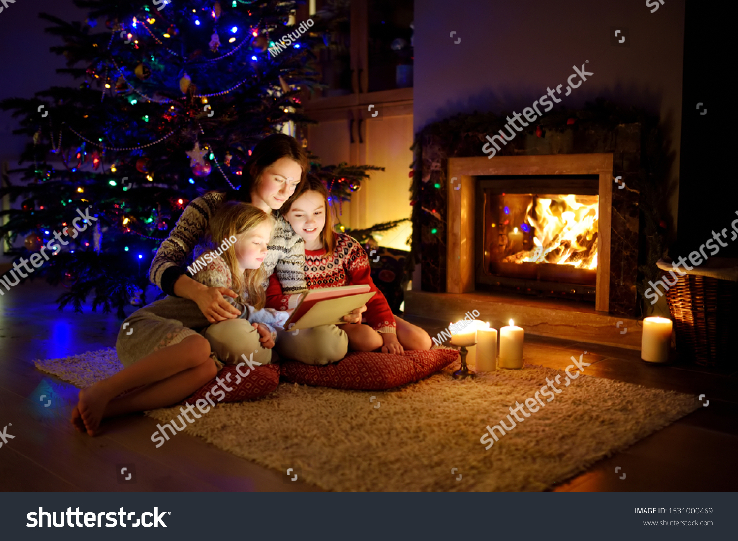 Mother and her two cute young daughters using a tablet pc at home by a fireplace in warm and cozy living room on Christmas eve. Winter evening at home with family and kids. #1531000469