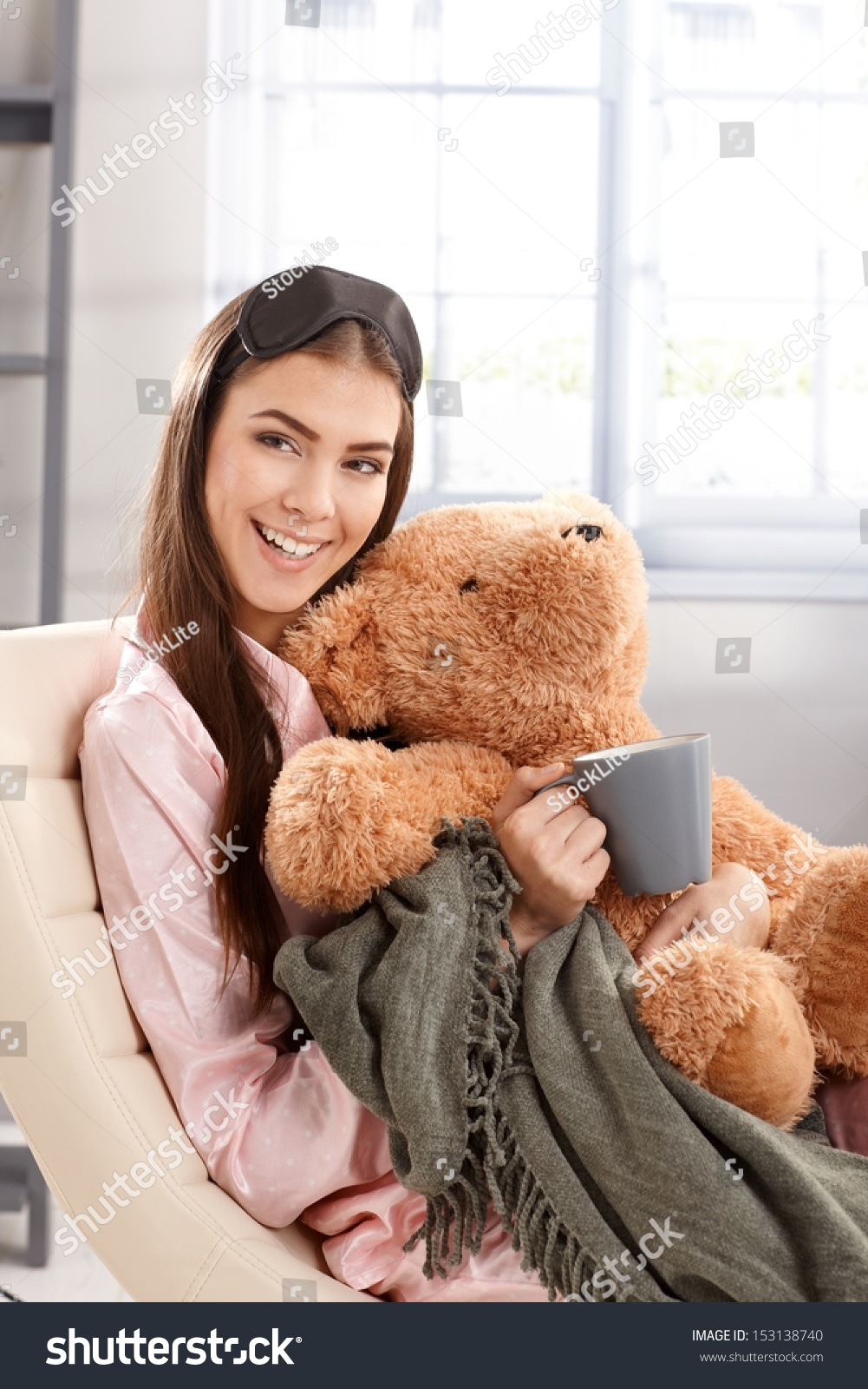 0e7908169b Morning portrait of laughing woman cuddling with teddy bear and blanket at  home