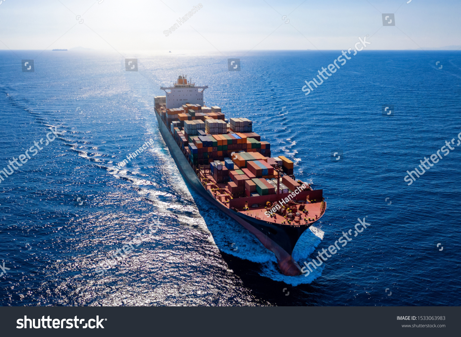 Aerial view of a heavy loaded container cargo vessel traveling in full speed over blue ocean