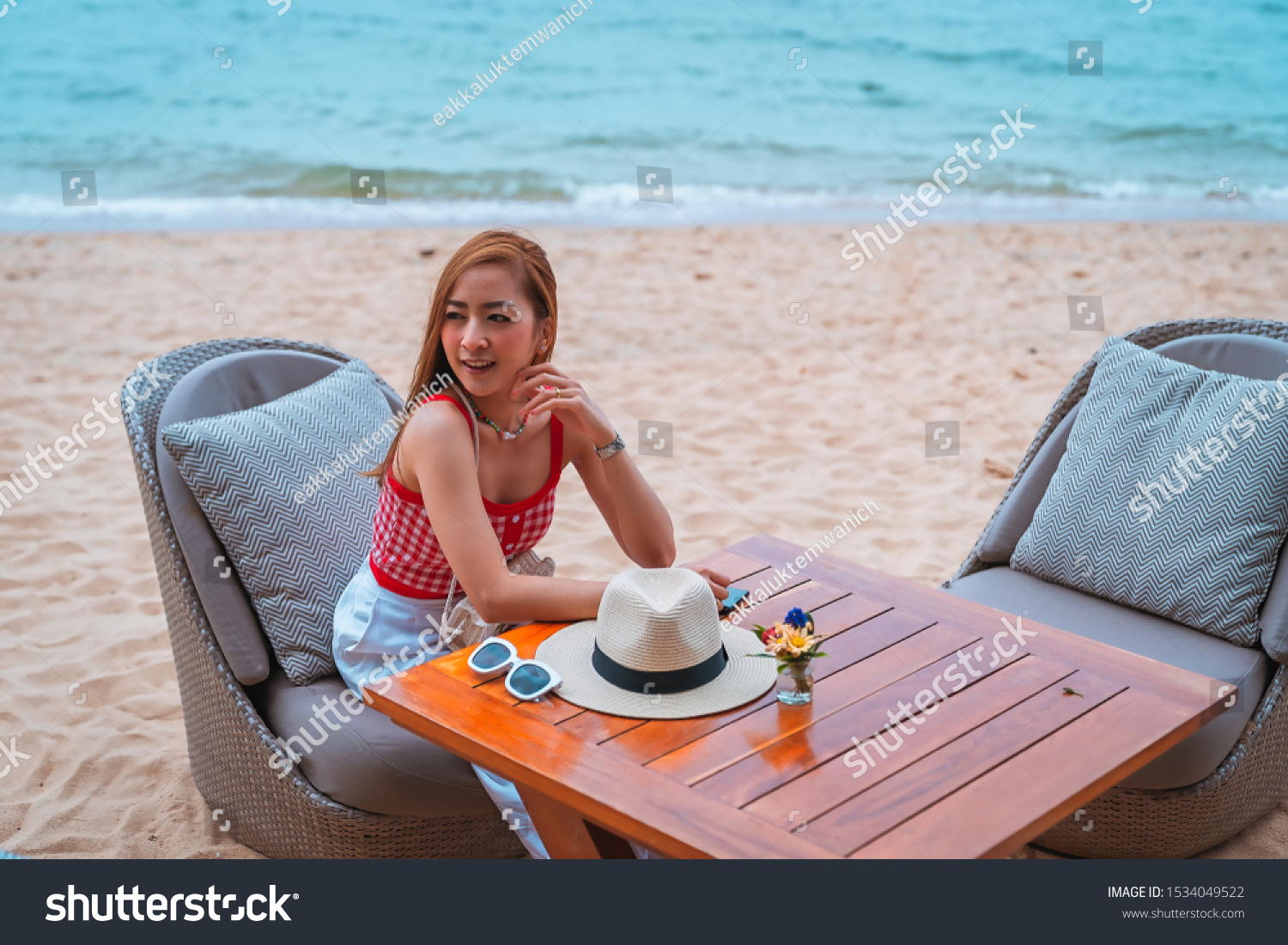 traveler girl in red dress sit on the chair in beach with vacation trip in emotional relax and smile for relax concept #1534049522
