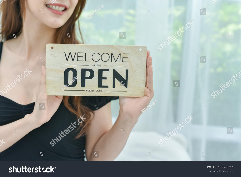 Store Owner Turning Open Sign In Shop Doorway #1535489312