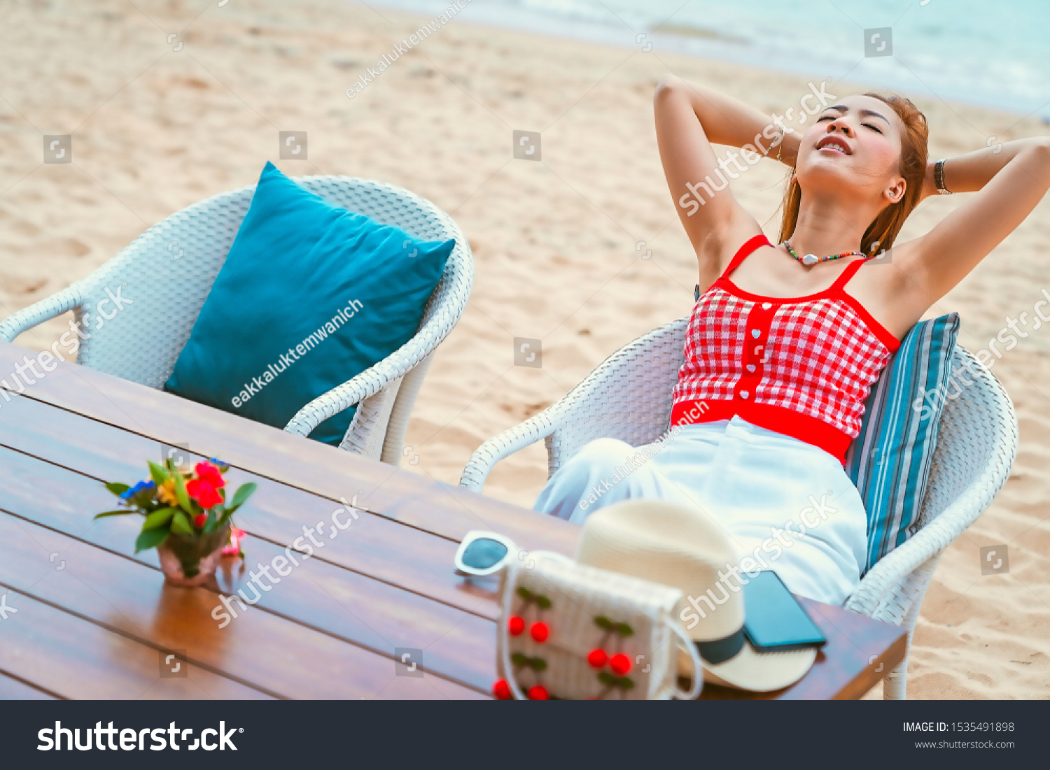 traveler girl in red dress sit on the chair in beach with vacation trip in emotional relax and smile for relax concept #1535491898