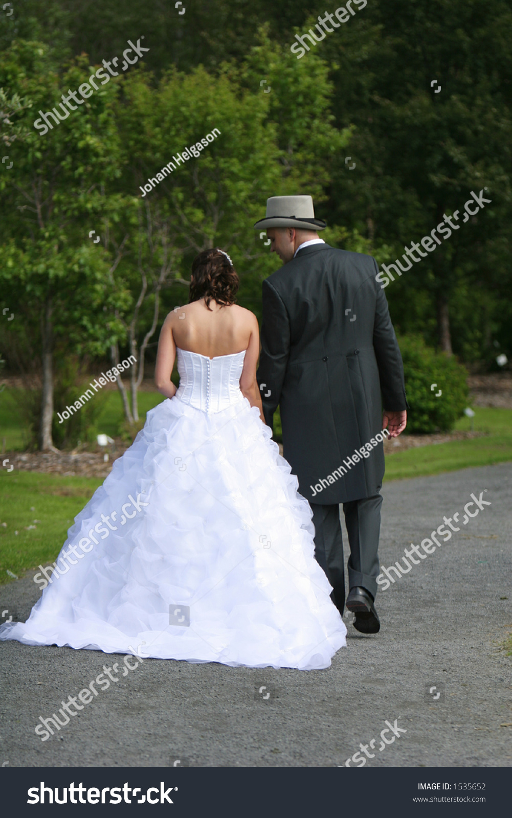 Newlyweds Walking Through A Botanic Garden After The Ceremony Enjoying A Quiet Moment Alone