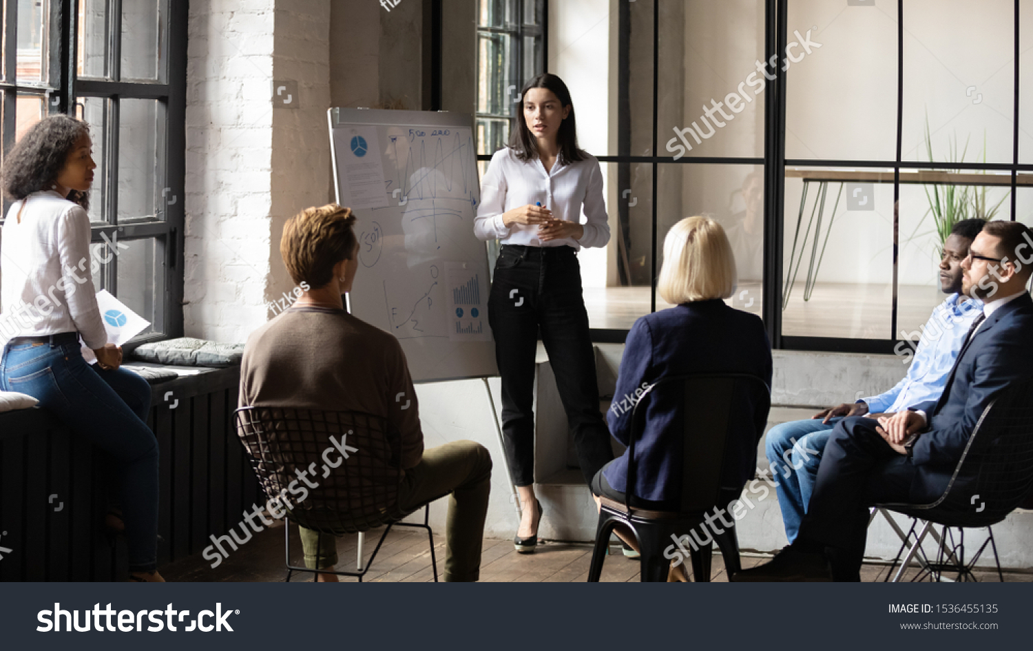 Confident lady business trainer coach leader give flip chart presentation consulting clients teaching employees training team people speaking explaining strategy at marketing workshop concept #1536455135