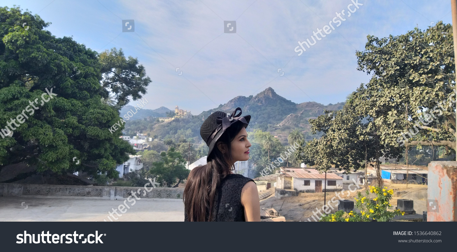 young girl with hat enjoying beautiful day at mount abu, Rajasthan . Tourist traveler, mountain view background on trip of Rajasthan country India