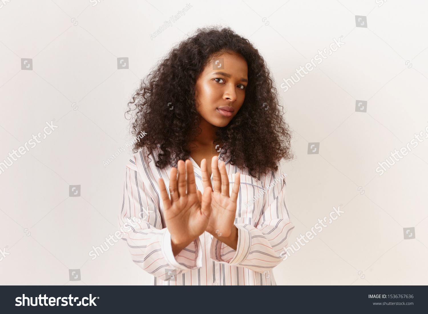 Human facial expressions and body language. Studio image of scared displeased young female in striped pajamas expressing negative reaction, reaching out palms, saying No or Stop, being annoyed #1536767636
