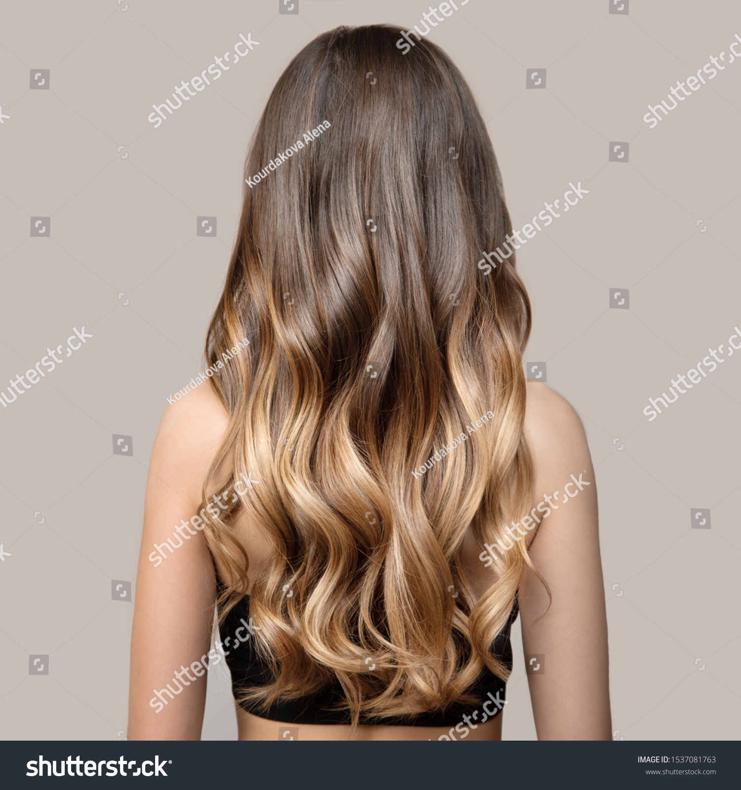Portrait of a beautiful young brunette woman with long wavy hair. Back view. #1537081763