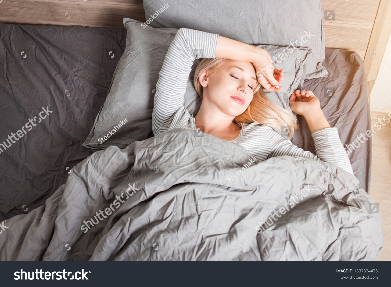 Caucasian beautiful restful blonde woman lying in bed and sleeping peacefully in morning, enjoying comfort and softness of bedclothes, wearing striped sleepwear. Good rest and bed time. Top view. #1537324478