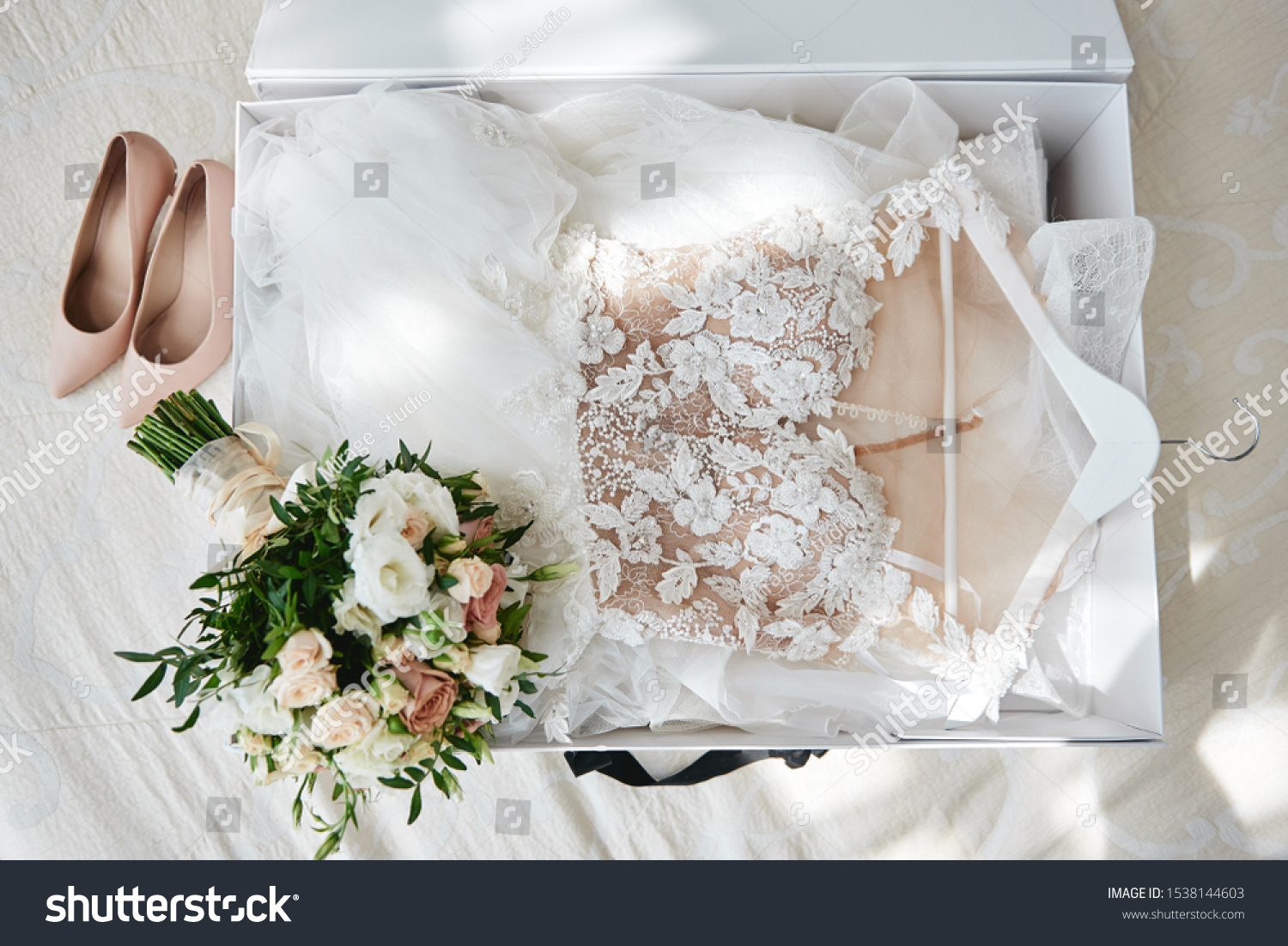 Luxury wedding dress in white box, beige women's shoes and bridal bouquet on bed, copy space. Bridal morning preparations. Wedding concept #1538144603