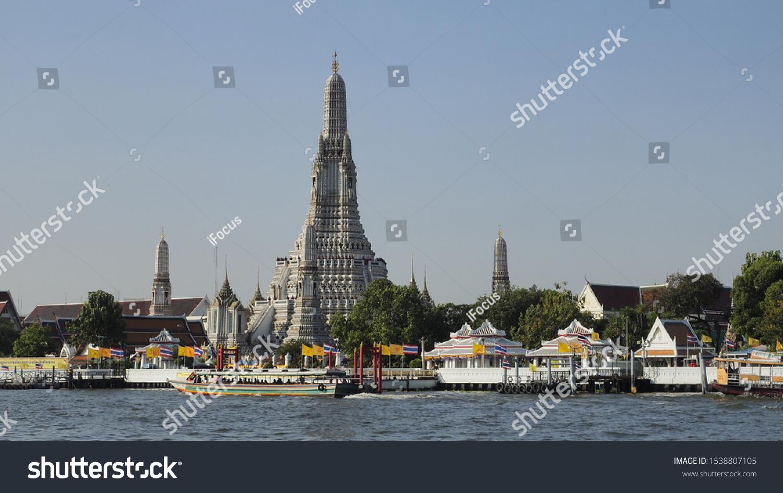 BANGKOK, THAILAND - OCTOBER 21, 2019: A passenger boat passes in front of Wat Arun on October 21, 2019 in Thai capital Bangkok.