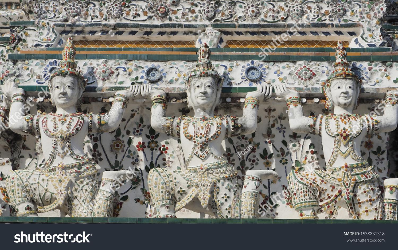 Guard statues on the base of a prang at Wat Arun, the Temple of Dawn in Bangkok