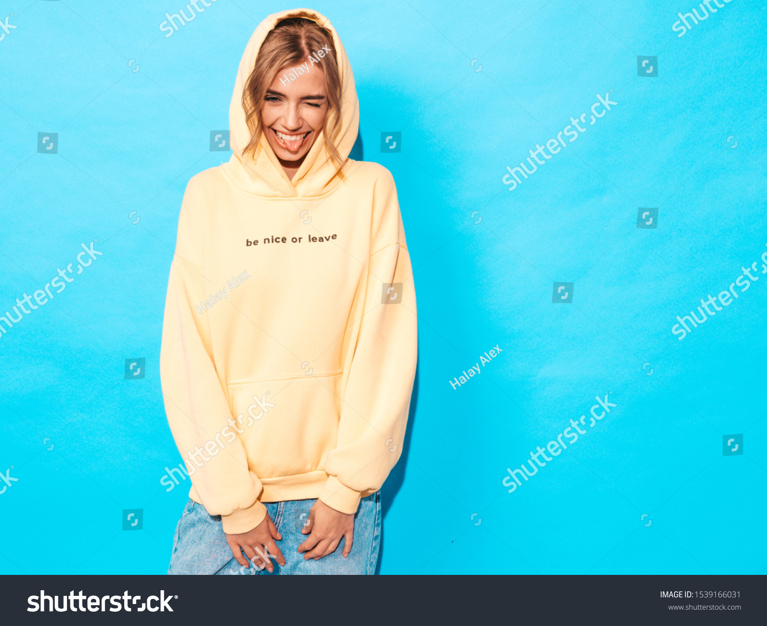 Portrait of young beautiful smiling girl in trendy summer hipster yellow hoodie.Sexy carefree woman posing near blue wall. Positive model having fun.Winks and shows tongue #1539166031