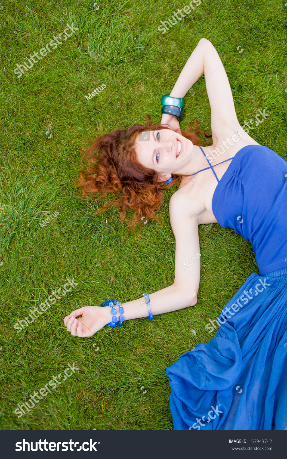 Up view of smiling 20s redhead women weared blue tank top, laying down in the fresh summer grass and having summertime fun and enjoyment, art bracelets on the hand