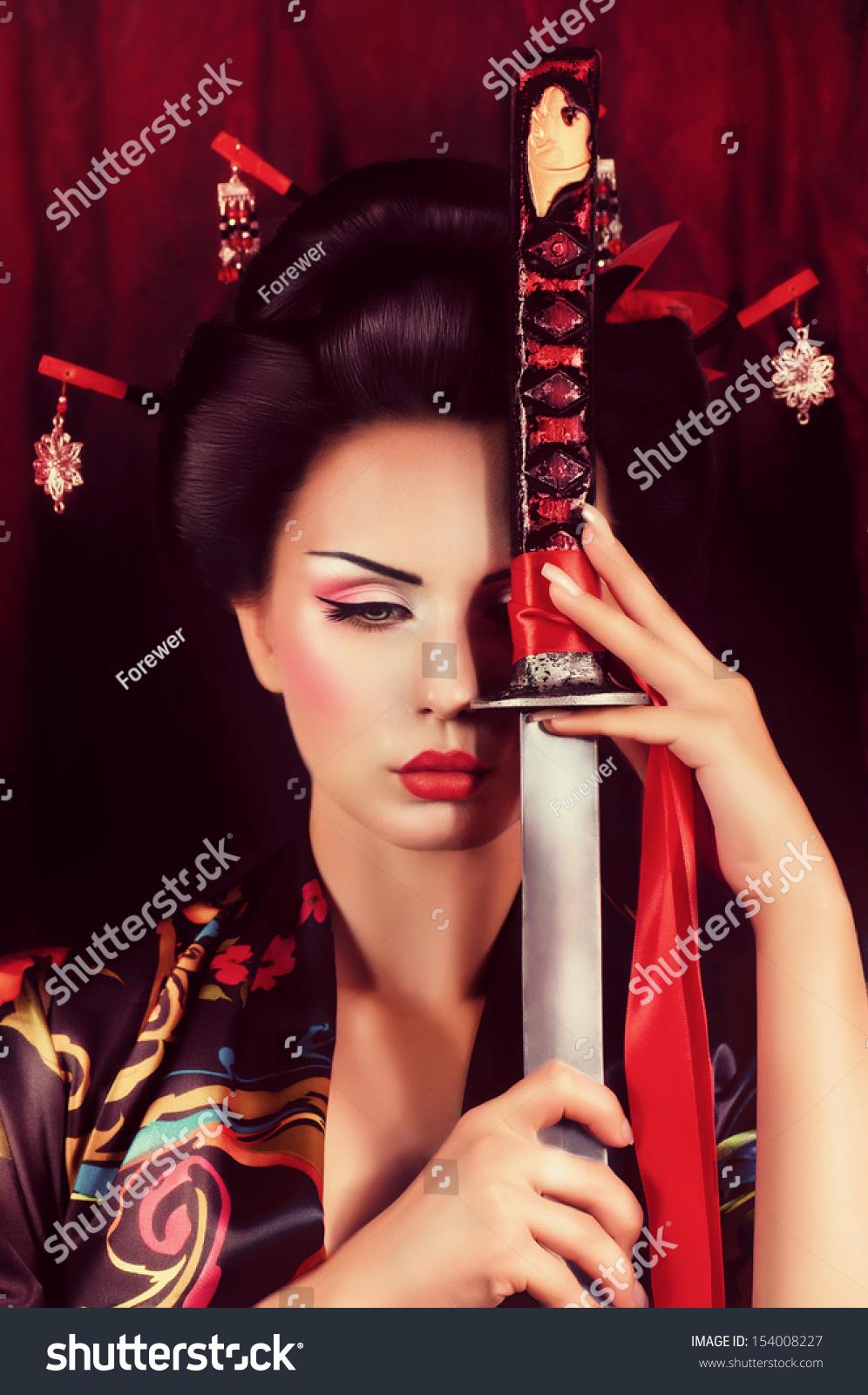 Beautiful Geisha In Kimono With Samurai Sword Stock Photo
