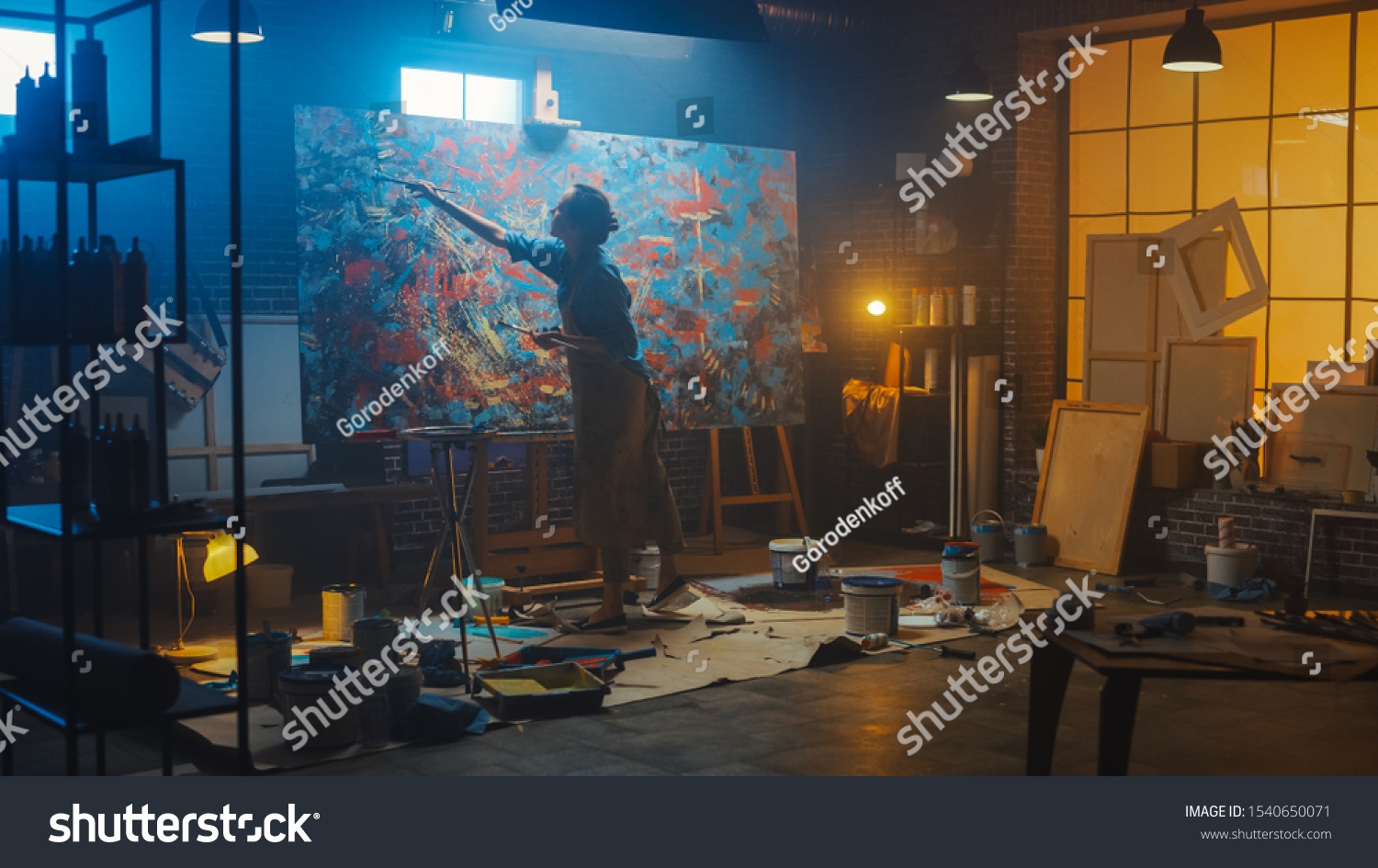 Talented Female Artist Works on Abstract Oil Painting, Using Paint Brush She Creates Modern Masterpiece. Dark and Messy Creative Studio where Large Canvas Stands on Easel Illuminated #1540650071
