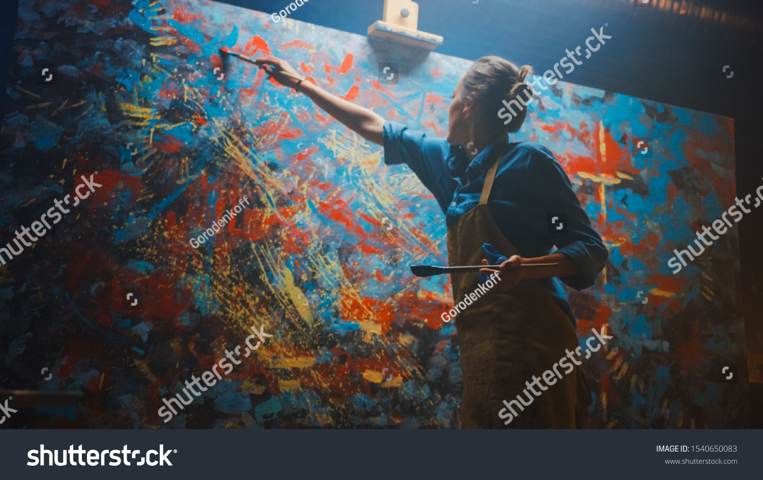 Talented Female Artist Energetically and Enthusiastically Using Paint Brush She Creates Modern Masterpiece of the Oil Painting. Creative Studio with Large Canvas of Striking Colors. Low Angle Shot #1540650083