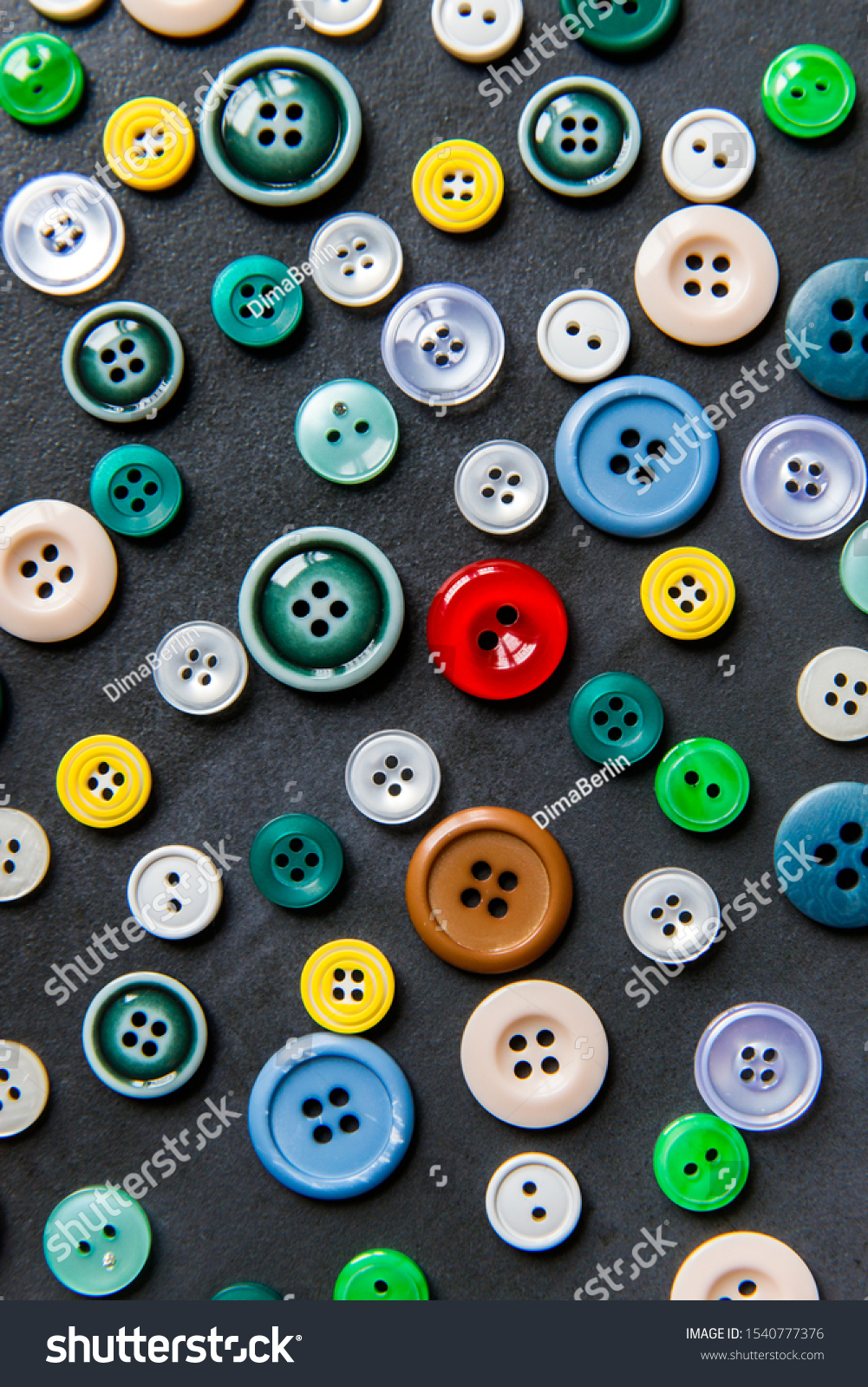 Colorful mixed sewing buttons on black background, flat lay. Top view.