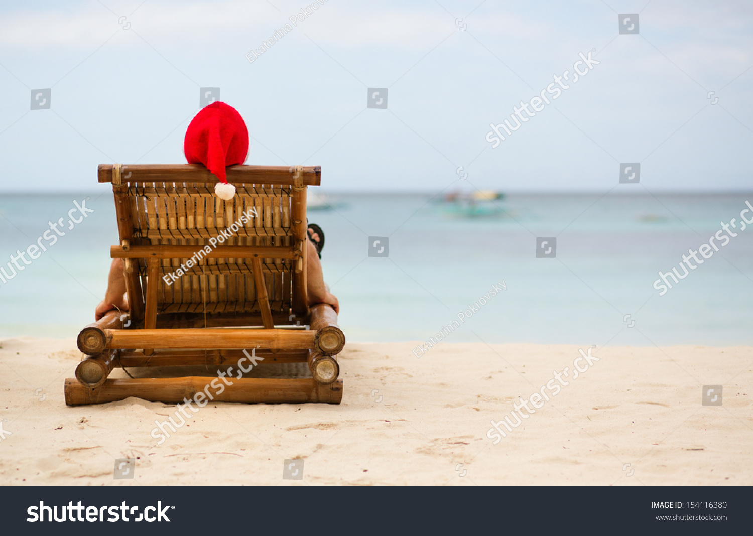 Santa sitting on chaise longue on white sand beach stock for Beach chaise longue