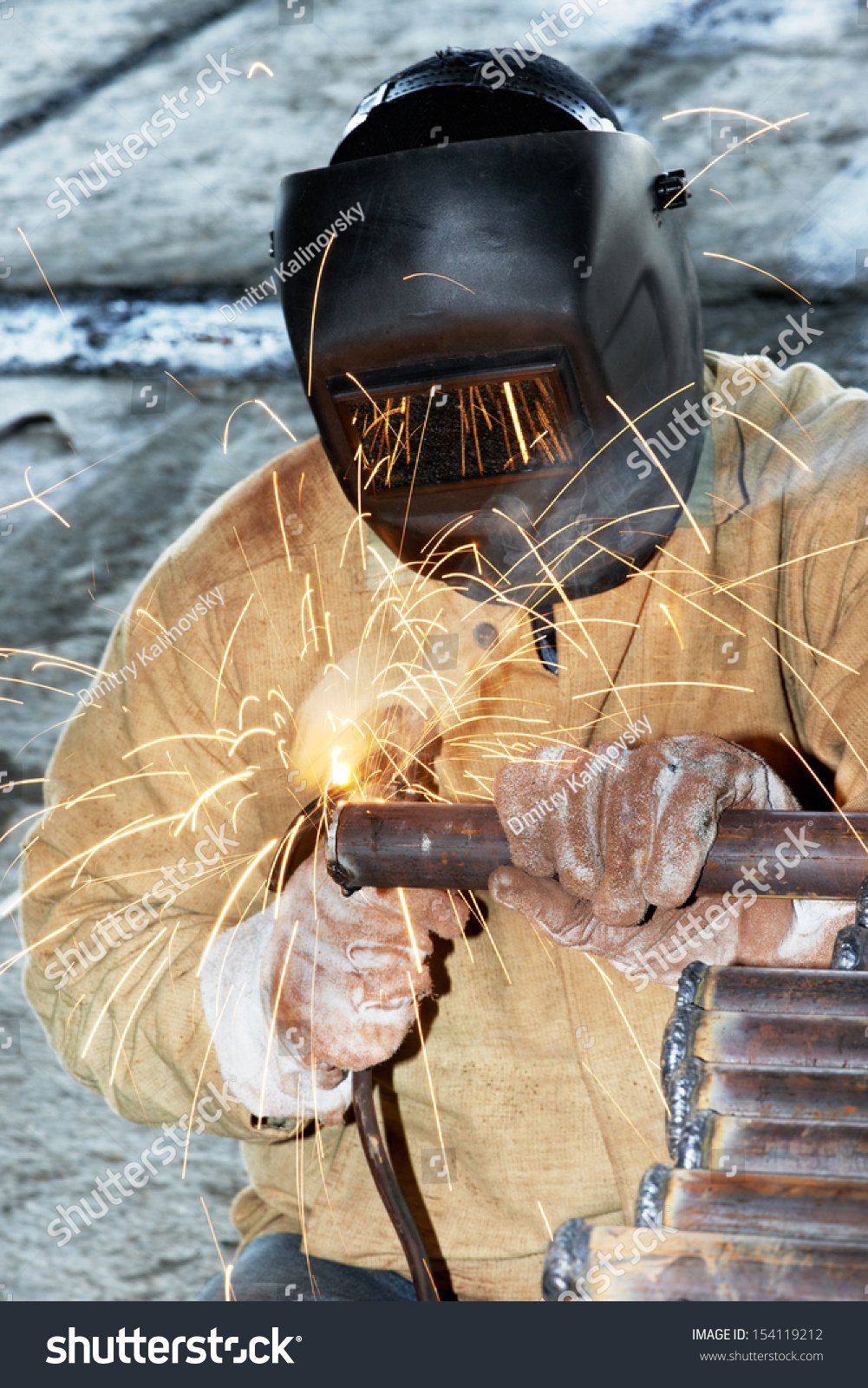 welder worker welding metal by electrode with bright electric arc and sparks during manufacture. Black Bedroom Furniture Sets. Home Design Ideas