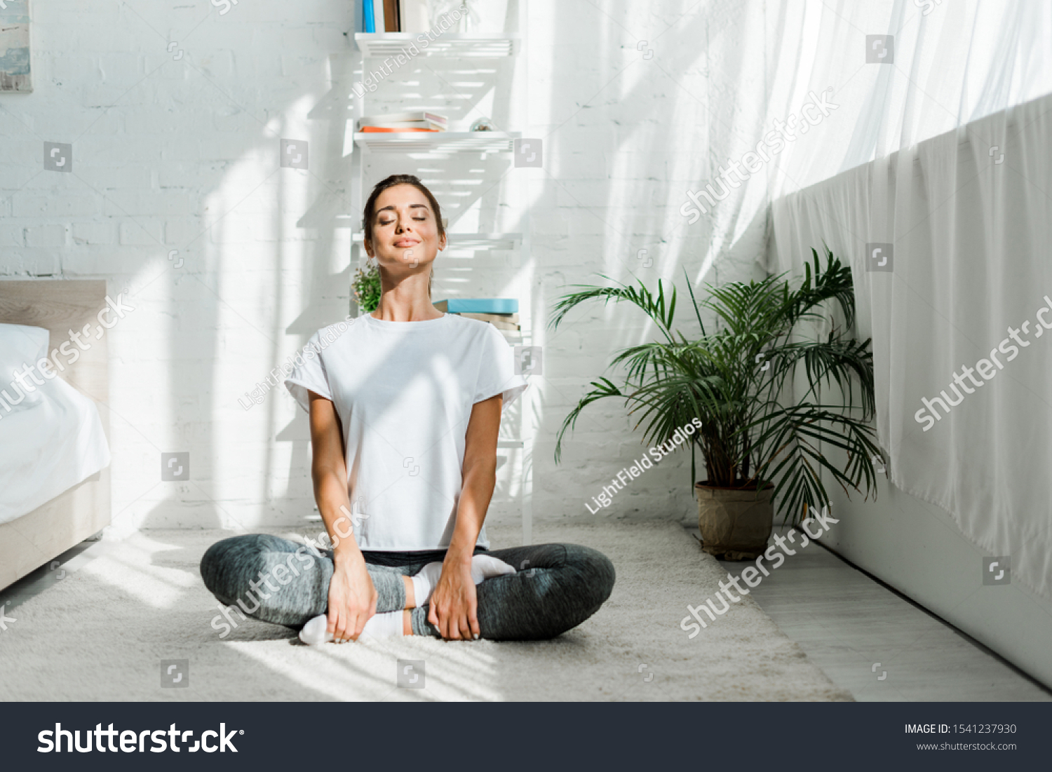 beautiful happy girl with closed eyes practicing yoga in lotus position in bedroom in the morning  #1541237930