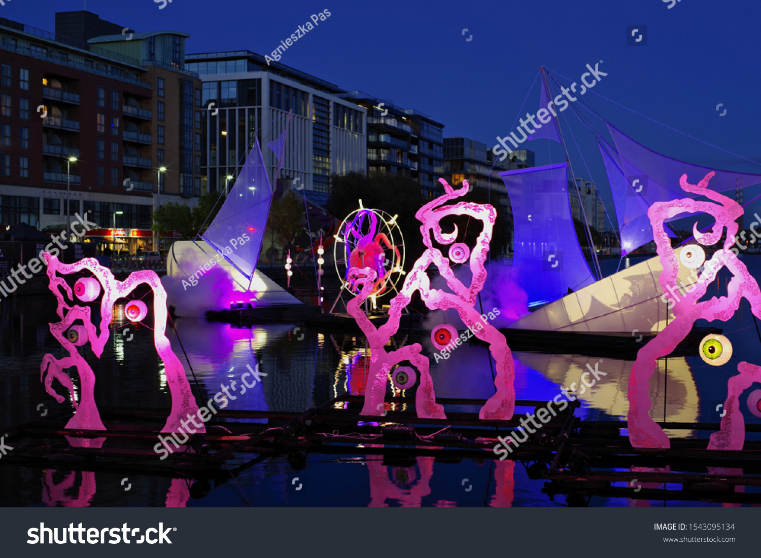 DUBLIN, IRELAND - OCTOBER 27, 2019: Night Watch in pink and blue. Sound and visual installation on the water. The Bram Stocker Festival in Dublin. Halloween.