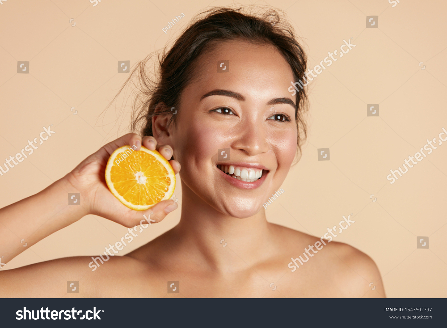 Beauty. Smiling woman with radiant face skin and orange portrait. Beautiful smiling asian girl model with natural makeup, healthy smile and glowing hydrated facial skin. Vitamin C cosmetics concept #1543602797