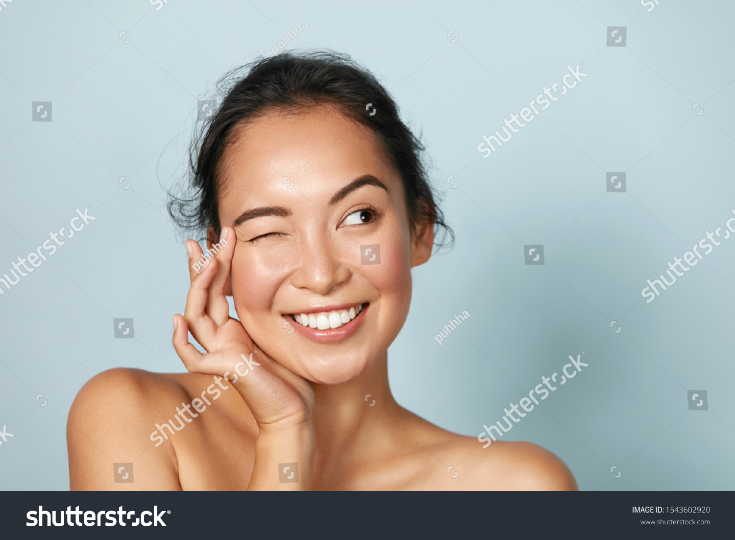 Skin care. Woman with beauty face touching healthy facial skin portrait. Beautiful smiling asian girl model with natural makeup touching glowing hydrated skin on blue background closeup #1543602920