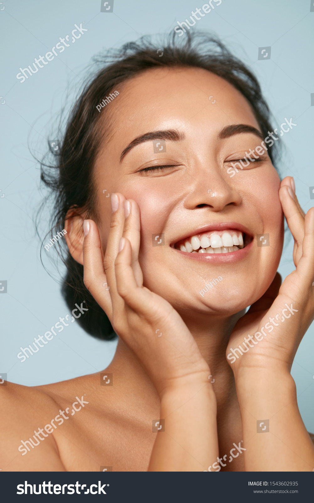 Skin care. Woman with beauty face touching healthy facial skin portrait. Beautiful smiling asian girl model with natural makeup touching glowing hydrated skin on blue background closeup #1543602935