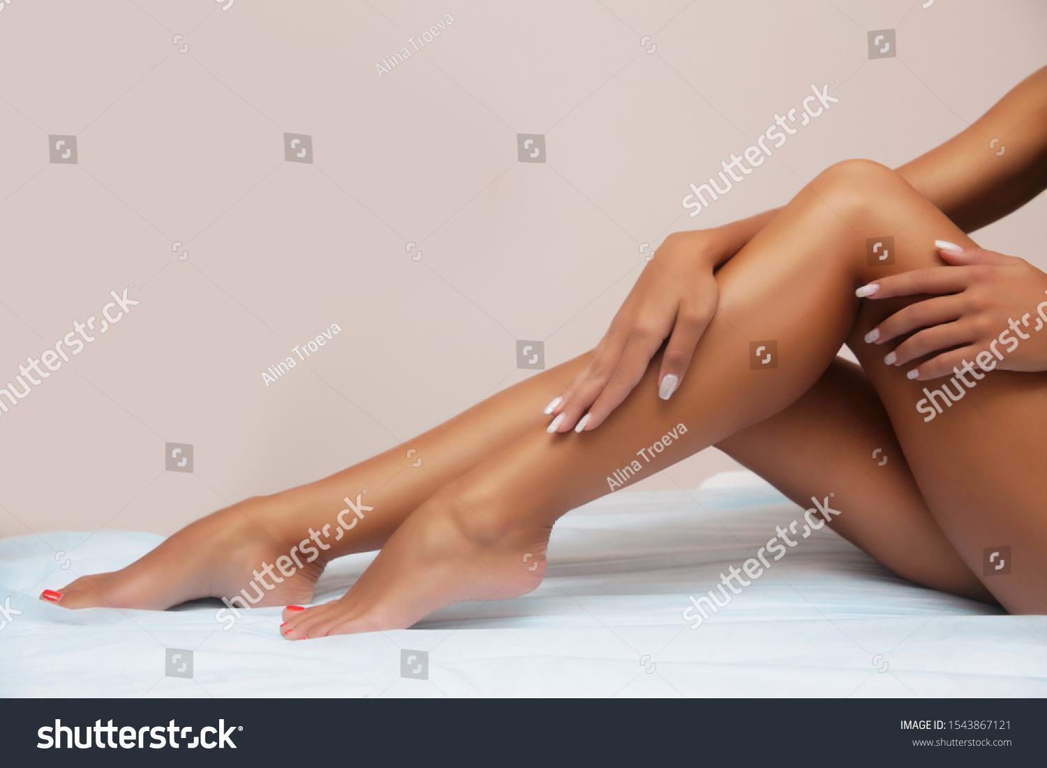 Woman body care. Close up of long female tanned legs with perfect smooth soft skin, pedicure, healthy nails on white background. Epilation, beauty and health concept  #1543867121