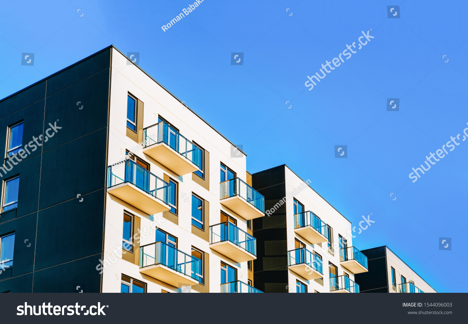 Fragment of Modern residential apartment with flat buildings exterior. Detail of New luxury house and home complex. Part of City Real estate property and condo architecture. Copy space. Blue sky #1544096003