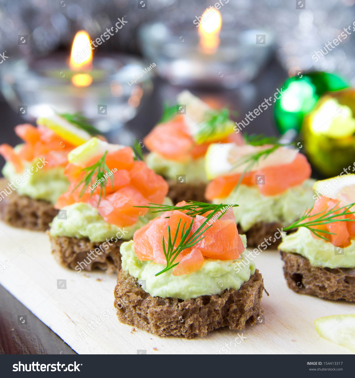 Delicious appetizer canapes of black bread avocado and for Canape table