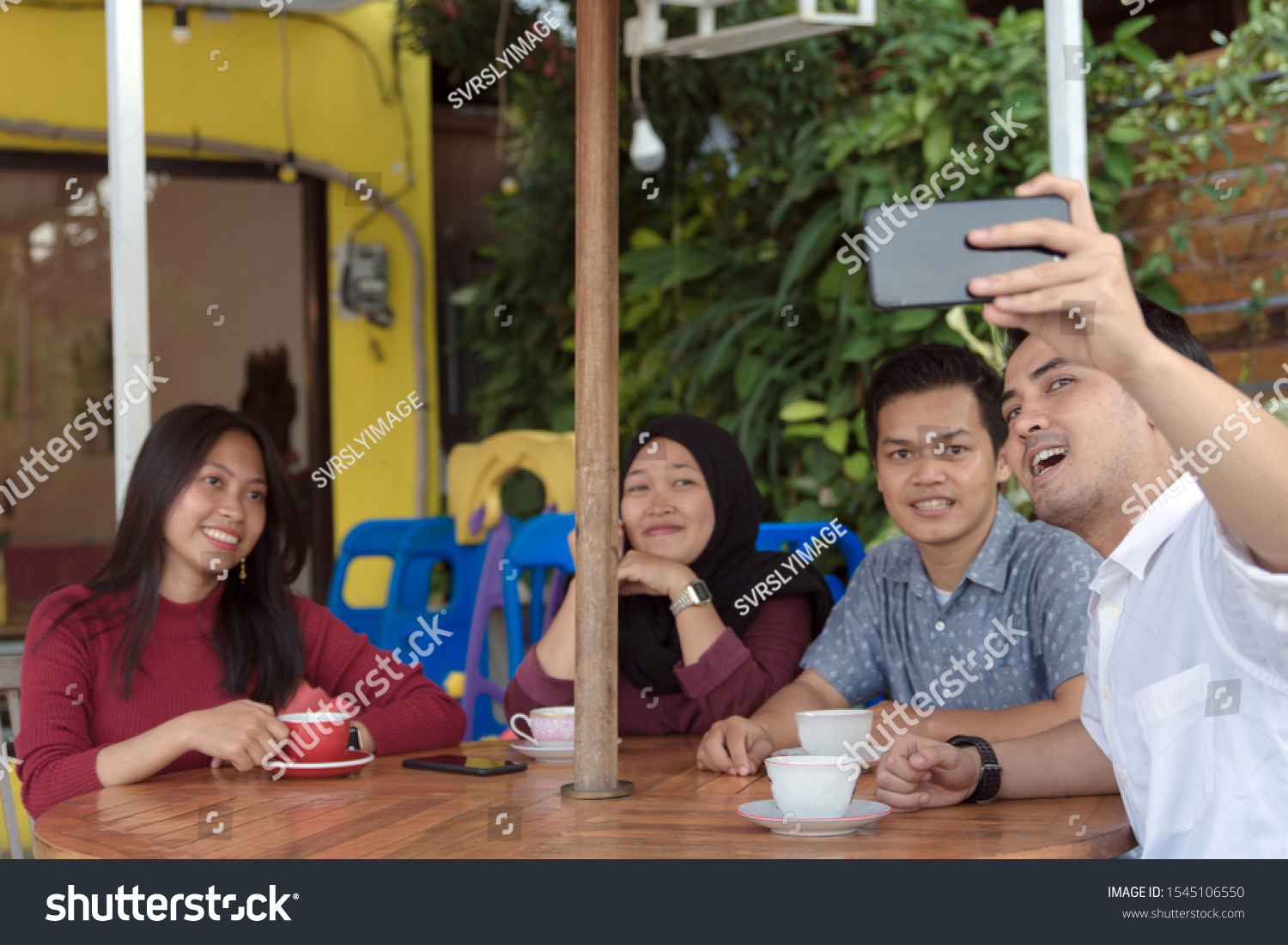 Multiracial group of four asian friends having a coffee together. Two women and two men at cafe, talking, laughing and enjoying their time while taking group selfie. #1545106550