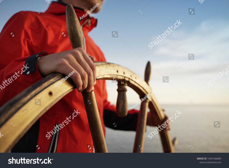 Man Holding Hands on ship rudder and navigates.  #1545166883