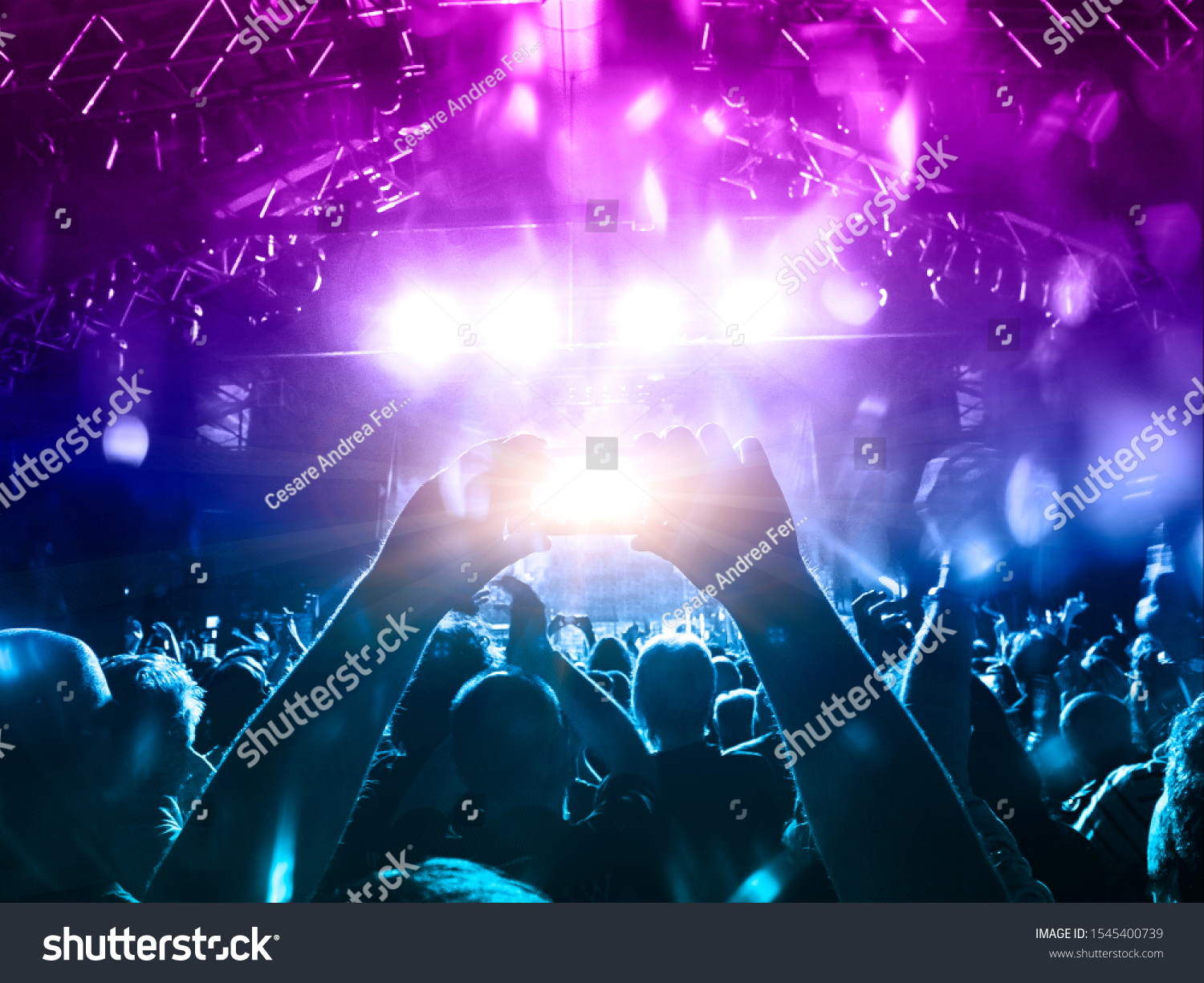 Concert hall crowded with people in front of a stage lit for the gig #1545400739