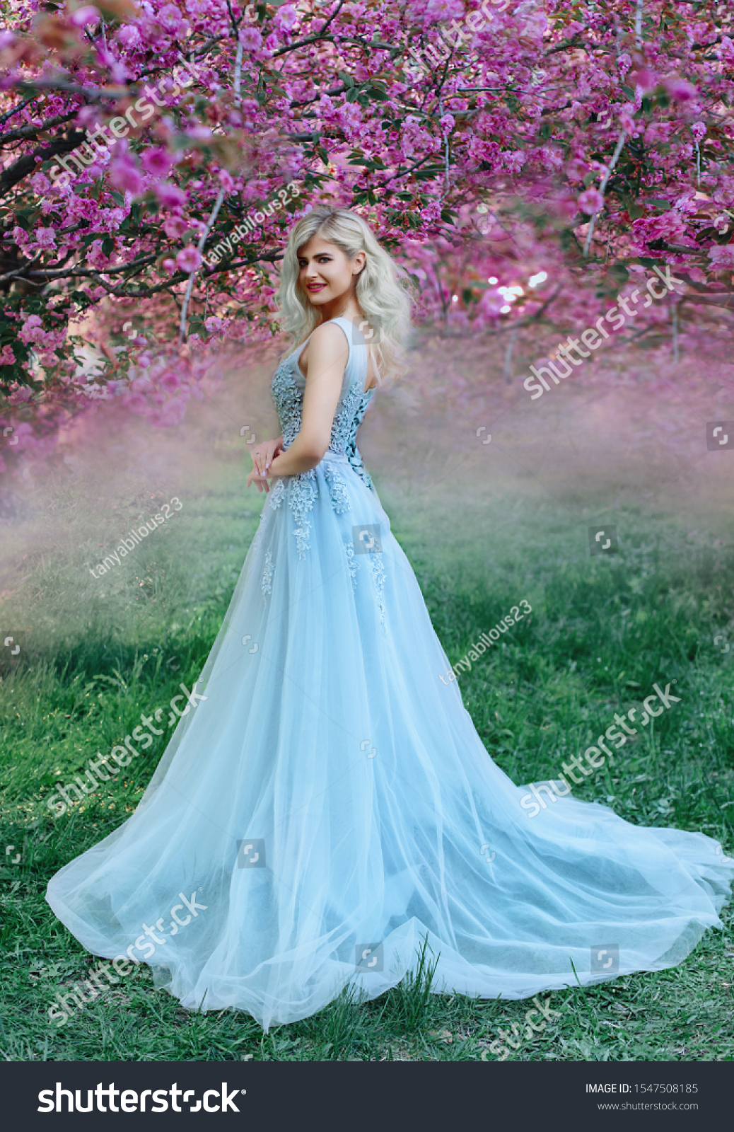 An incredible, delicate blonde in a luxurious, delicately blue dress walks in the spring, sakura and cherry orchards are in bloom. Princess with long curly hair. Vanilla color art photo #1547508185