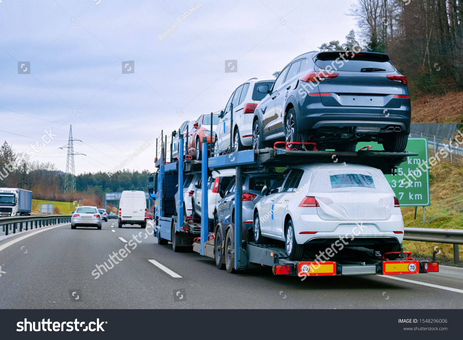 Car carrier transporter truck on road. Auto vehicles hauler on driveway. European transport logistics at haulage work transportation. Heavy haul trailer with driver on highway. #1548296006