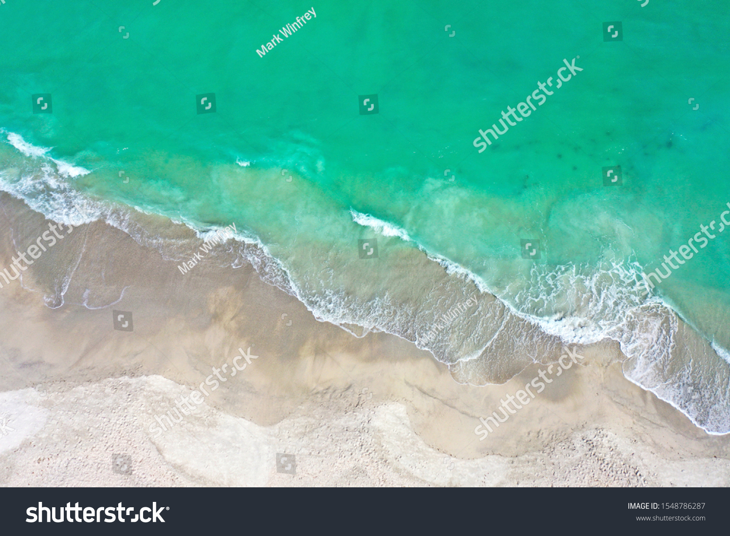 Aerial Photo of the Beach of Anna Maria Island with the Ocean Surf Coming Ashore.