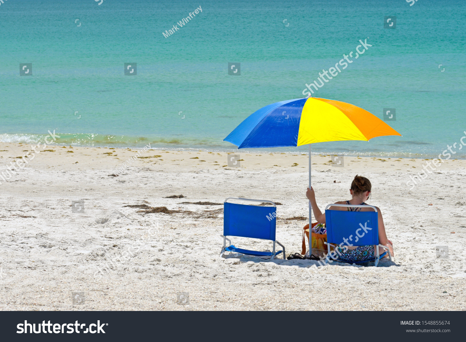 Unidentifiable Woman Sitting in the Shade of a Colorful Beach Umbrella while Enjoying a Relaxing Day at the Beach