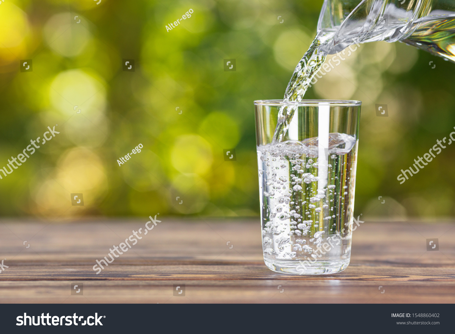 water from jug pouring into glass on wooden table outdoors #1548860402
