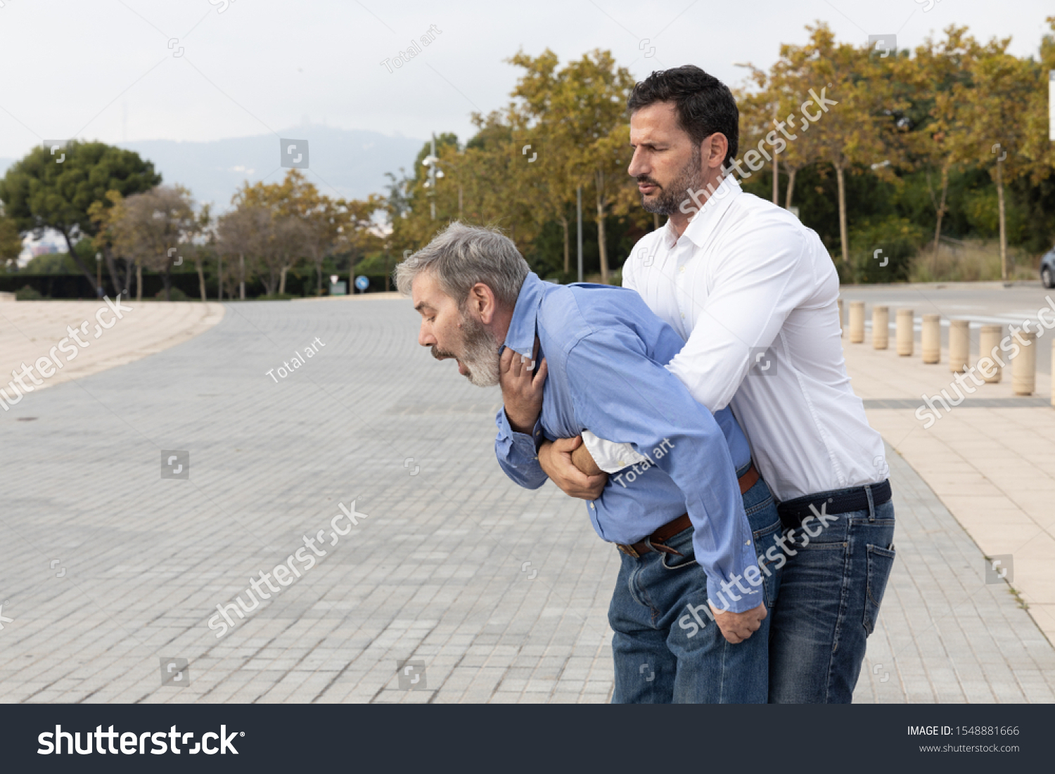 Man doing the Heimlich maneuver to an old man with suffocation due to obstruction of the airway with food #1548881666